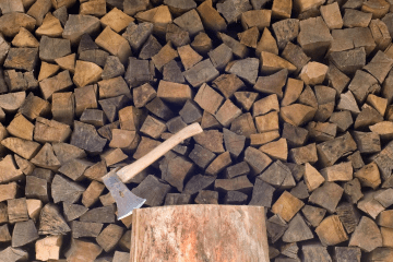 Image of best burning fire pit firewood stacked with an axe in the foreground