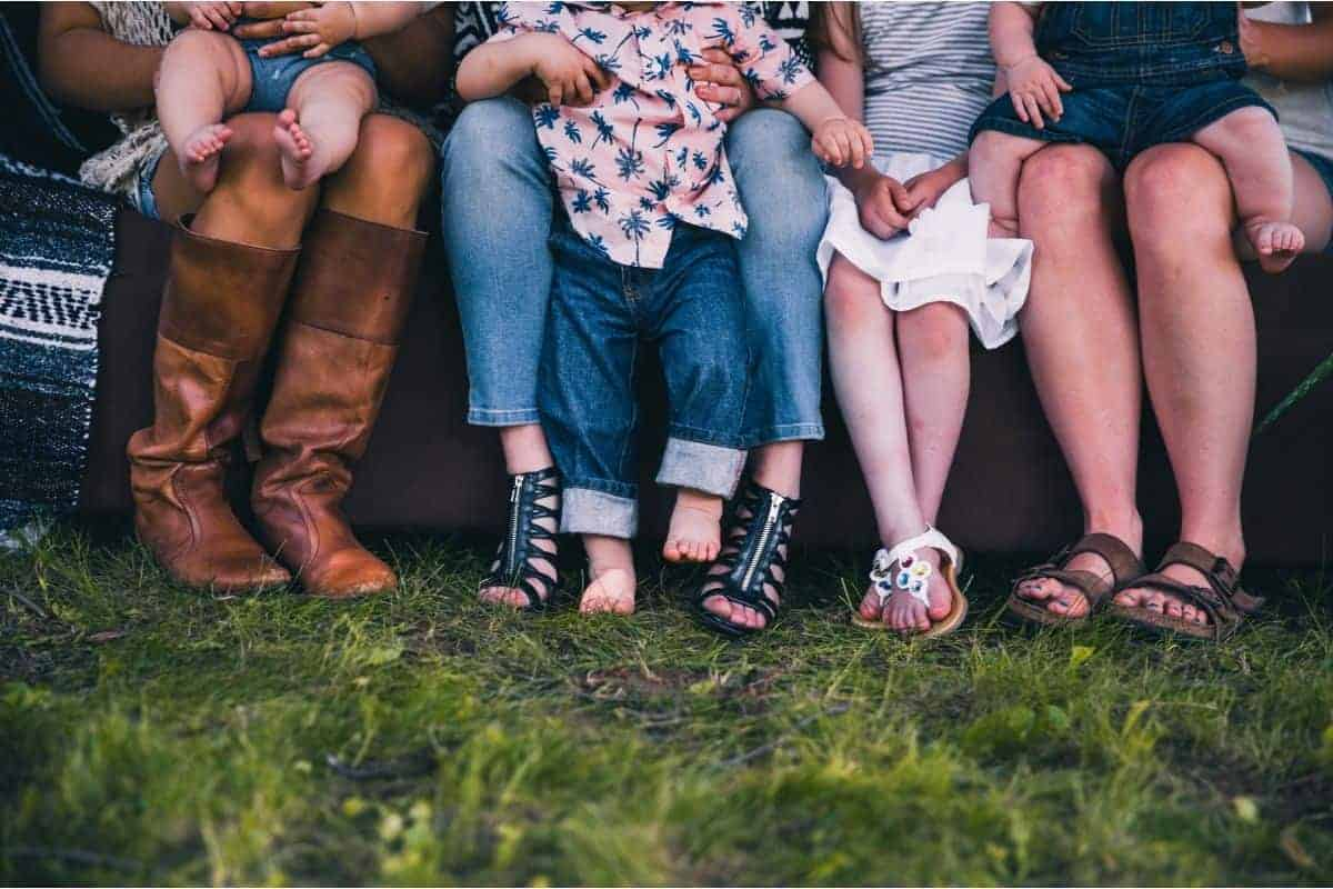Image of people sitting near a fire pits on grass