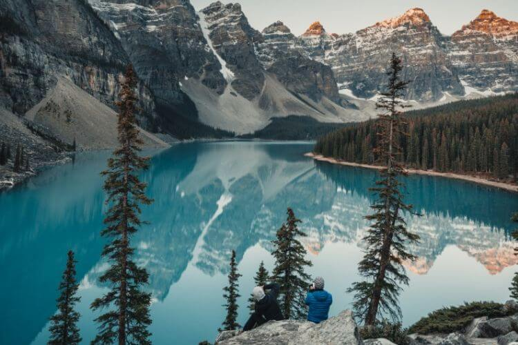 Image of two people sitting on a rock in front of a mountain lake talking about me