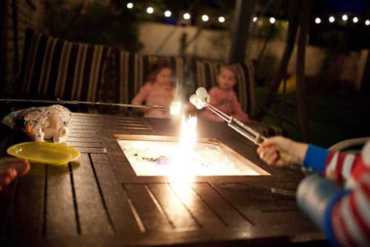Image of children roasting marshmallows over a propane fire pit at night