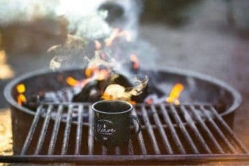Image of smoky fire pit, a grill grate and a coffee cup