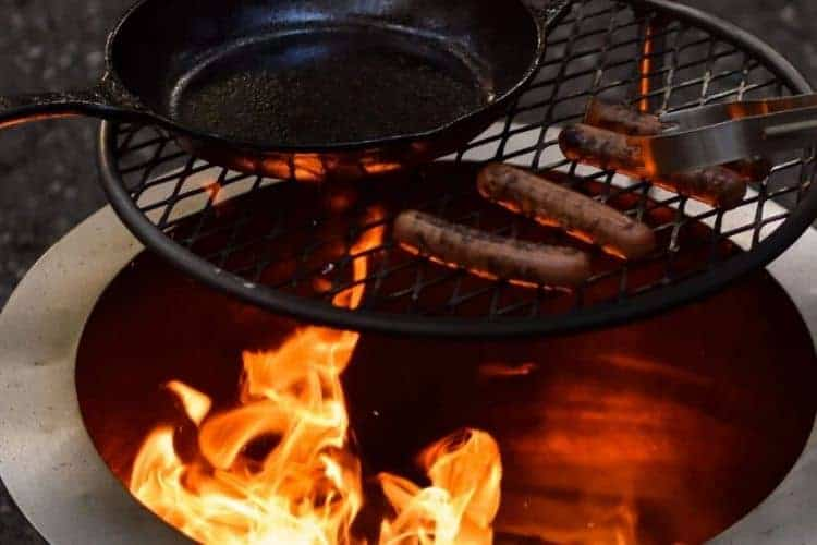 Image of hot dogs grilling on a fire pit