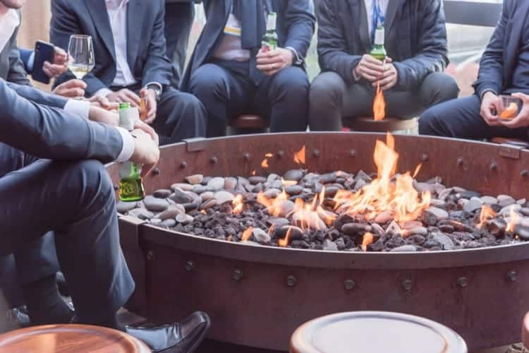 Image of men sitting around wondering what are fire pits round