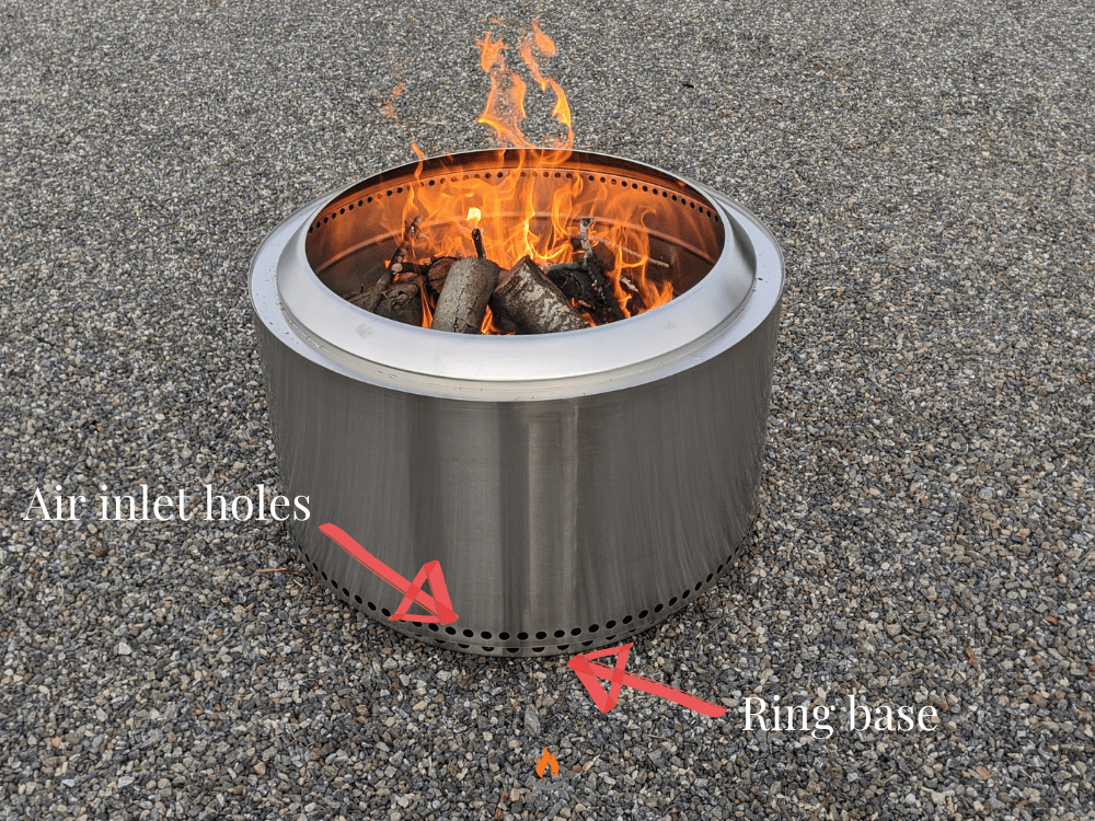 Image of a burning Solo Stove fire pit on a stone driveway.